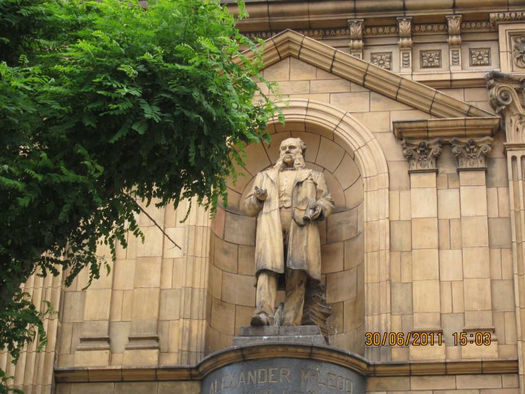 Full length statue of Alexander McLeod standing in niche on front of the Royal Arsenal Co-operative Society building.